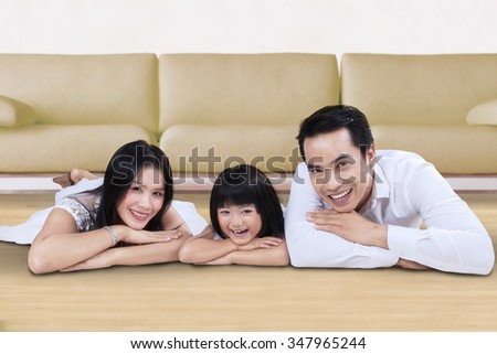 Photo of cheerful family lying on the floor while smiling at the camera near the sofa at home - stock photo
