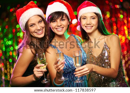 Photo of cheerful girls looking at camera with smiles while enjoying Christmas party