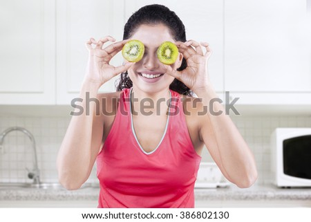Photo of cheerful Indian woman holding two slices of kiwi fruit in front of her eyes in the kitchen - stock photo