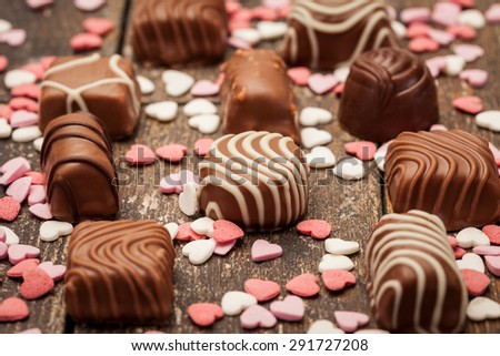 Photo of chocolate pralines over wooden table - stock photo