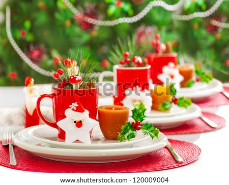 Photo of Christmas table decoration, festive dinnerware with candles and red cups for tea in decorated dinner room, luxury utensil, New Year party, Christmastime table setting, xmas decor - stock photo