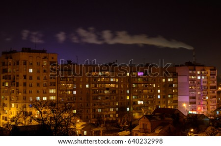 Photo of city buildings at night with factory smoke above them