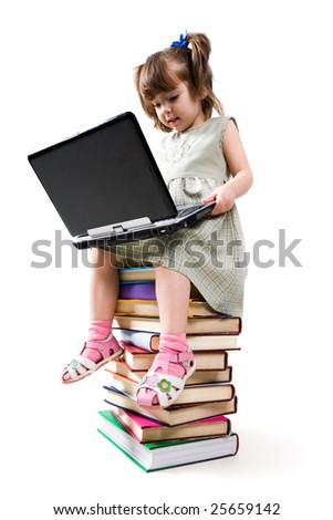 Photo of clever child with laptop on her knees looking at its keypad