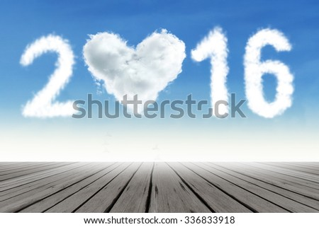 Photo of cloud shaped numbers 2016 and heart symbol on the sky above wooden floor. New year concept - stock photo