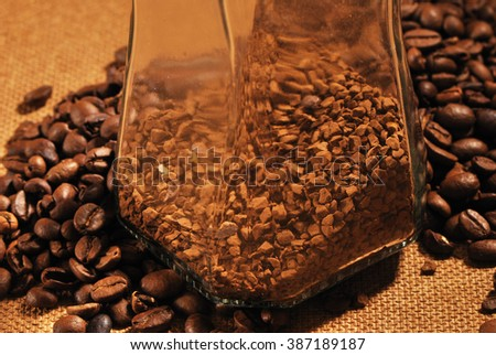 photo of coffee beans and glass jar with instant coffee on brown background