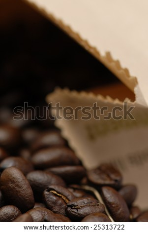Photo of coffee beans spilling out of a paper bag.