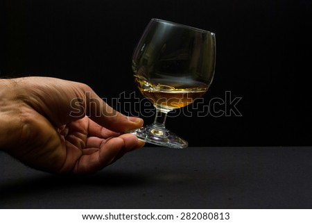 Photo of cognac glass in human hand against black background