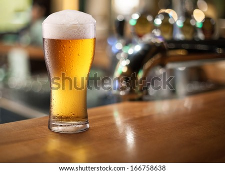 Photo of cold beer glass on a bar. Closeup. - stock photo
