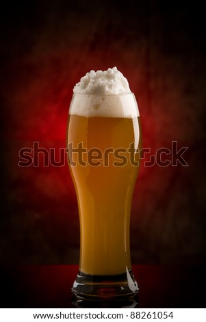 photo of cold delicious beer in front of a rural background