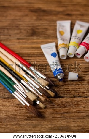 Photo of Collection of brushes and acrylic colors on old wooden board with visible grooves - stock photo