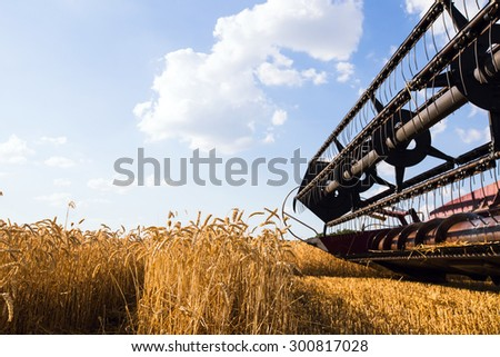 Photo of combine harvester that is harvesting wheat - stock photo