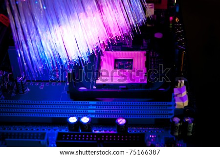 Photo of computer motherboard with fiber optics background