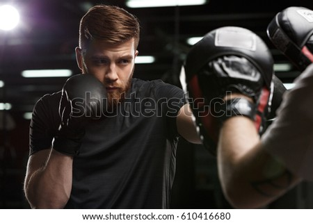 Photo of concentrated handsome young strong sports man boxer make exercises in gym with trainer and looking aside.
