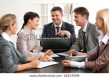 Photo of confident business people looking at woman while planning work at meeting