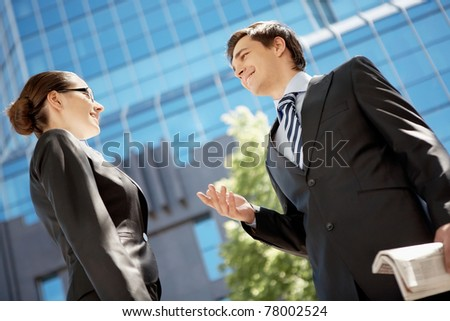 Photo of confident businessman looking at associate while communicating with her