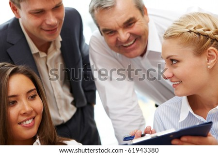 Photo of confident businesswoman showing plan to co-workers - stock photo