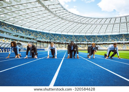 Photo of confident multi ethnic business people lined up getting ready for race on modern sport track. Stadium as a background - stock photo