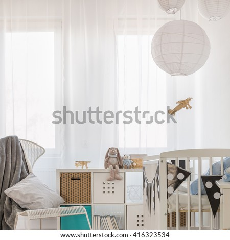 Photo of cosy toddler bedroom with crib and cabinet - stock photo