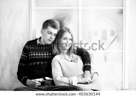 photo of Couple of teenagers sitting against mirror wall - stock photo