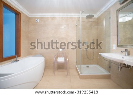 Photo of cozy beige bathroom with shower and bathtub