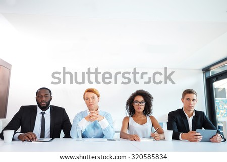Photo of creative multi ethnic business group. Mixed race business team or commission with electronic devices seriously looking at camera while judging. White modern office interior - stock photo