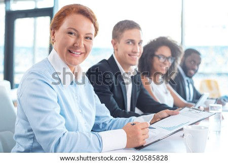 Photo of creative multi ethnic business group. Mixed race business team using electronic devices, looking at camera, smiling, and sitting in row. White modern office interior with big window