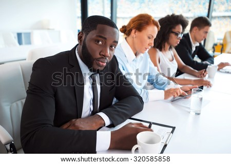 Photo of creative multi ethnic business group. Mixed race business team using electronic devices and working. Accent on African businessman. White modern office interior with big window - stock photo