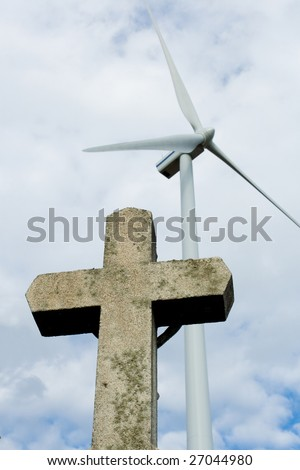Photo of cross standing at the field with Wind power on the background - stock photo