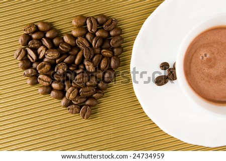Photo of cup of coffee with shape of heart made of beans near by - stock photo