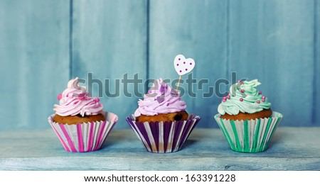 Photo of 3 cupcakes on wooden background - stock photo