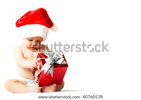 Photo of curious and surprised baby in Santa cap looking at giftbox in his hands