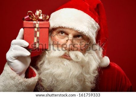 Photo of curious Santa Claus with giftbox keeping it by his ear