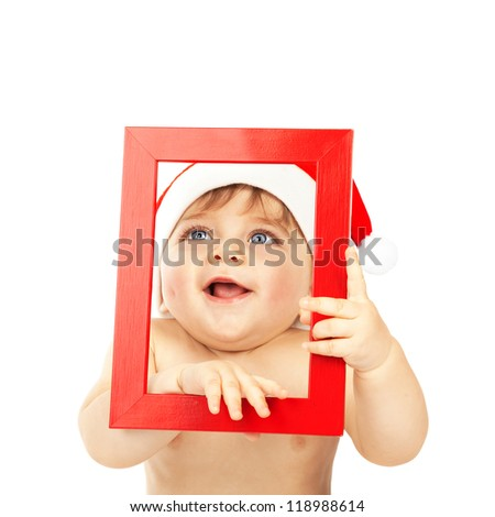 Photo of cute baby boy wearing Santa Claus hat, adorable child holding red frame in hands looking through it, pretty small kid isolated on white background, Christmas eve, New Year celebration - stock photo