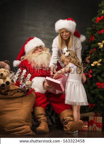 Photo of cute girl and her mother and Santa Claus holding giftbox and opening it at home near Christmas tree - stock photo