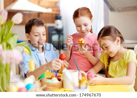 Photo of cute kids painting Easter eggs at home - stock photo