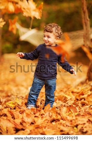 Photo of cute little boy enjoying autumnal nature, pretty infant playing in park, cheerful baby boy having fun outdoors, adorable kid in fall forest, happy child play with dry orange maple leaves - stock photo