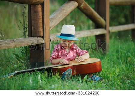 photo of cute little cowboy playing guitar - stock photo