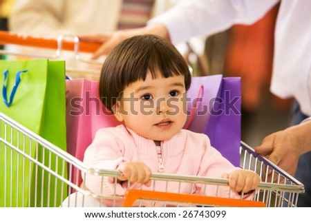 Photo of cute little girl looking upwards while sitting in handcart in the mall - stock photo