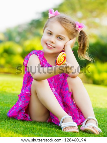 Photo of cute little girl sitting on green grass on backyard and holding in hand colorful lollipop, small child wearing pink dress outdoors in spring and eating sweet sugar candy, happy childhood - stock photo