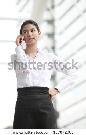 Photo of cute young business woman talking on her smartphone,Serious