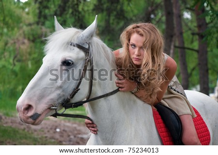 Photo of cute young girl astride on a beautiful horse somewhere in forest