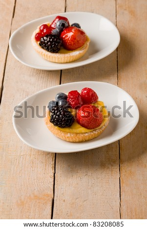 photo of delicious pastry with cream and berries on wooden table