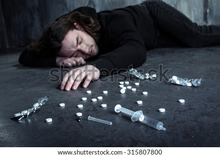 Photo of desperate young drug addict lying alone in dark after taking heroin and pills - stock photo