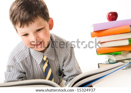 Photo of diligent schoolchild reading book with stack of textbooks near by - stock photo