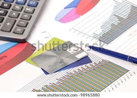 Photo of document some graphics & pen and calculator and credit cards