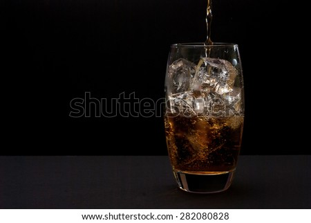 Photo of drink pouring into glass full of ice against black background