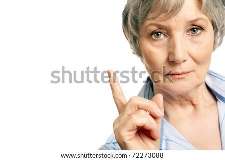 Photo of elderly female with her forefinger pointed upwards on white background - stock photo