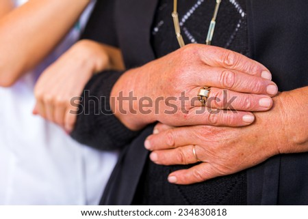 Photo of elderly woman hands supported by young carer hands - stock photo