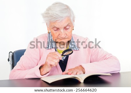 Photo of elderly woman reading a book  - stock photo