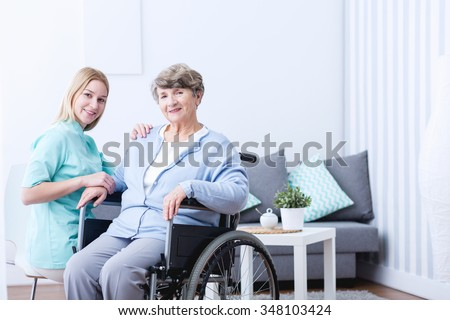 Photo of elderly woman with disability and caregiver - stock photo